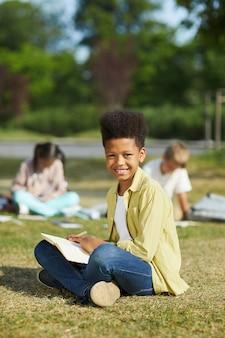 緑の芝生の上に座って、日光の下で屋外のクラスを楽しみながらカメラを見ている笑顔のアフリカ系アメリカ人の少年の縦長の肖像画、コピースペース