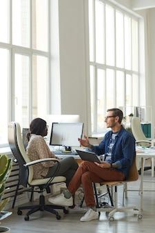 Вертикальный портрет в полный рост улыбающегося современного бизнесмена, разговаривающего с афро-американским коллегой при использовании компьютера в белом офисе, копией пространства