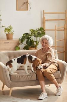 Вертикальный портрет в полный рост улыбающейся пожилой женщины, играющей с собакой и угощающей ее, сидя на диване в уютном домашнем интерьере