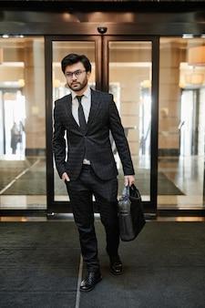 비즈니스 여행에 호텔 로비에 들어가는 성공적인 중동 사업가의 세로 전체 길이 초상화