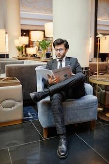 호텔 로비의 안락의자에 앉아 문서를 읽는 성공적인 중동 사업가의 세로 전체 길이 초상화
