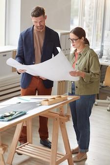 Вертикальный портрет в полный рост двух архитекторов, держащих чертежи и обсуждающих работу, стоя у чертежного стола в офисе