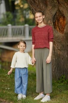 Вертикальный полный портрет двух сестер, держащихся за руки, стоя в парке на открытом воздухе
