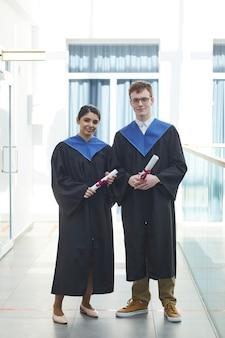 Вертикальный портрет в полный рост двух молодых людей в выпускных платьях и смотрящих в камеру, стоя в помещении в современном университетском интерьере