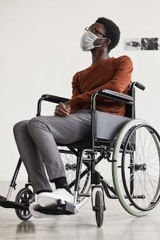 現代アートギャラリーで絵画を見ながら車椅子を使用し、マスクを着用している若いアフリカ系アメリカ人男性の縦長の肖像画