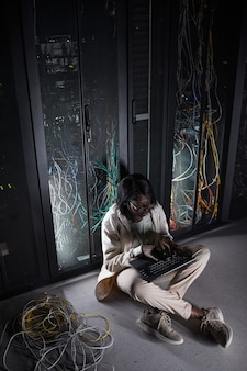 Вертикальный портрет в полный рост молодой афро-американской женщины, сидящей на полу в серверной и использующей ноутбук во время работы с суперкомпьютером в центре обработки данных, копией пространства