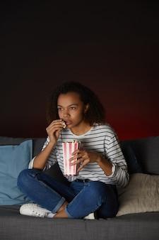 Вертикальный портрет в полный рост молодой афро-американской женщины, смотрящей телевизор дома и едящей попкорн, сидя со скрещенными ногами на диване в темной комнате