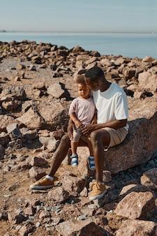 ビーチでかわいい息子と遊ぶ若いアフリカ系アメリカ人の父の縦の完全な長さの肖像画