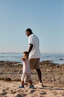 ビーチでの散歩を楽しんでいる赤ん坊の息子と若いアフリカ系アメリカ人の父の垂直の完全な長さの肖像画私は...