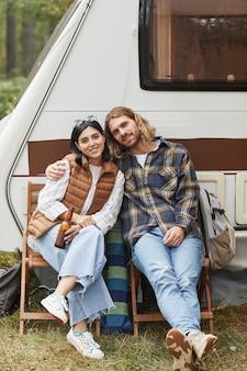 トレーラーバンとキャンプしながら屋外でリラックスする若いカップルの縦長の肖像画...