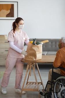 휠체어, 지원 및 음식 배달 개념을 가진 노인에게 식료품을 가져오는 젊은 여성 간호사의 세로 전체 길이 초상화