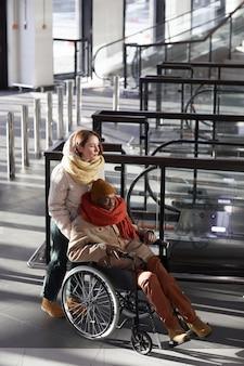 Вертикальный портрет в полный рост молодой женщины, помогающей афроамериканскому мужчине в инвалидной коляске на станции метро, копией пространства