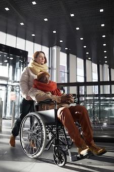 Вертикальный портрет в полный рост молодой женщины, помогающей афроамериканскому мужчине в инвалидной коляске на станции метро
