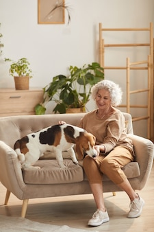 Vertical full length portrait of smiling senior woman playing with dog and giving him treats while sitting on couch in cozy home interior