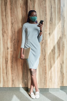 Vertical full length portrait of successful african-american businesswoman wearing mask and using smartphone while standing in sunlight by wood background