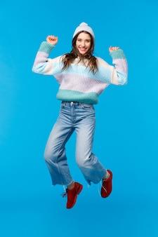 Вертикальный портрет в полный рост супер счастливая девушка прыгает от изумления, празднует новый год, рождественскую вечеринку, наслаждается праздниками, делает покупки с потрясающими большими скидками, жизнерадостная улыбка, синий фон