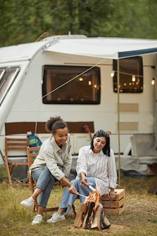 Vertical full length portrait of two young women relaxing by fire outdoors while camping with van in...