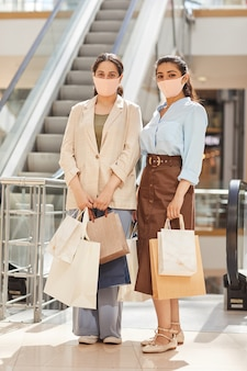 Vertical full length portrait of two young women wearing masks while shopping in mall and