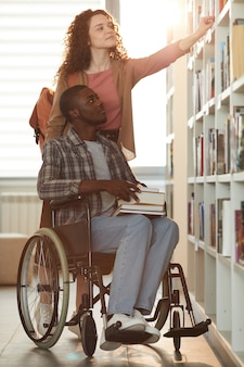 Vertical full length portrait of young african-american man using wheelchair in school with female friend helping him in library lit by sunlight