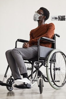Vertical full length portrait of young african-american man using wheelchair and wearing mask while looking at paintings in modern art gallery