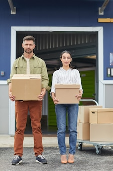 Vertical full length portrait of young couple holding boxes and  while standing by self storage facility