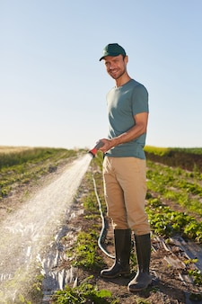 Vertical full length portrait of young male worker watering crops at vegetable plantation and smiling at camera while standing outdoors against blue sky