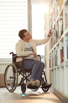 Vertical full length portrait of young man using wheelchair in school while looking at bookshelves in library lit by sunlight
