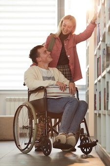 Vertical full length portrait of young man using wheelchair in school with female friend helping him in library lit by sunlight