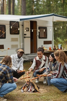 Vertical full length portrait of young people roasting marshmallows while enjoying camping with frie...