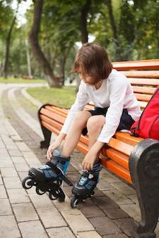 Vertical full length shot of a boy putting on rollerskates, sitting on park bench