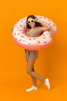 Colpo integrale verticale di ragazza splendida alla moda che gode del clima estivo di successo