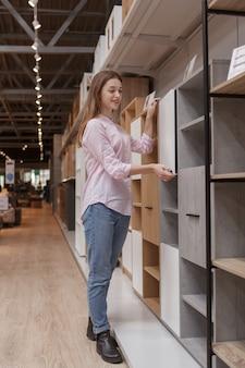 Вертикальный снимок в полный рост красивой женщины, покупающей новую мебель в универмаге