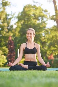 공원 잔디에 로터스 위치에 앉아 젊은 아름 다운 행복 한 여자의 세로 전체 길이 샷.