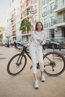 街の通りをサイクリングした後、屋外でリラックスし、コーヒーを飲む若い女性の垂直全長ショット