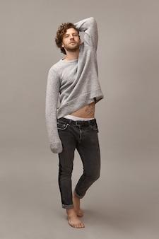 裸足でポーズをとって、スタイリッシュなデニムのズボンと灰色のジャンパーを身に着けて、入れ墨を示し、彼の胃を覆わないままにして、巻き毛の赤毛とひげを持つハンサムな若い男の垂直全長ショット
