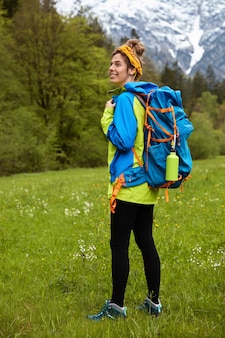 アクティブな服を着て、緑の牧草地をさまよう満足しているアクティブな女性観光客の垂直全長ショット