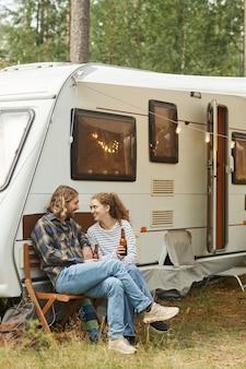キャンピングカーのバン警官とキャンプしながら屋外でピクニックを楽しんでいる若いカップルの垂直全長ショット...