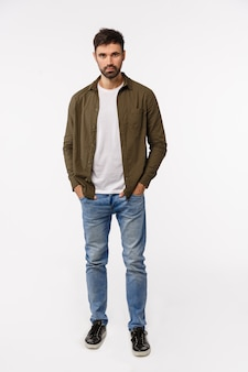 Vertical full-length shot sassy and confident modern man in coat, jeans streetstyle outfit, holding hands in pockets, looking assertive, smiling, getting ready business appointment, white background
