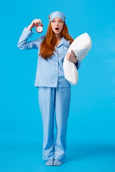 Vertical full-length shot shocked and startled cute redhead female in sleeping mask and pyjama, holding pillow and alarm clock, open mouth gasping worried, stare , blue wall