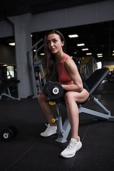Vertical full length shot of a sportswoman doing biceps curls with dumbbell at gym