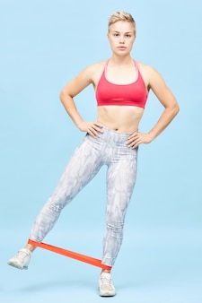 Vertical full length shot of sporty young blonde woman in stylish sports clothes training at blue wall with resistance band around her ankles, holding hands on her waist, lifting leg to side