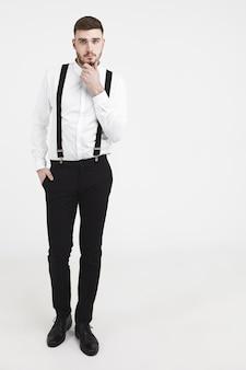 黒のズボン、靴、白いシャツを着たエレガントでハンサムな若いひげを生やした男性モデルの縦長のスタジオショット。サスペンダーが無精ひげに触れ、メンズウェアカタログのポーズをとっています。