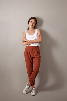 Vertical full length trendy looking fashionable young european woman dressed in white top, brown trousers and sneakers posing isolated, crossing arms confidently, enjoying leisure time