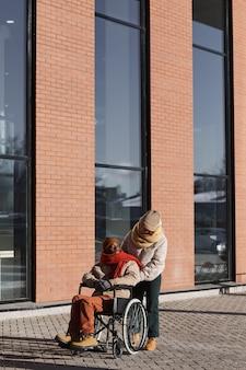 Вертикальный вид в полный рост на афроамериканца в инвалидной коляске, перемещающегося в городском городе с помощью молодой женщины, копией пространства