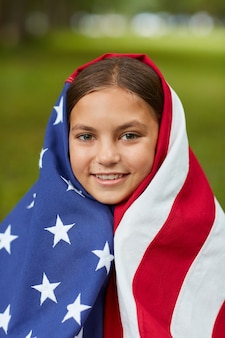 屋外の緑の芝生に座って笑っているアメリカの国旗に覆われたかわいい女の子の垂直フルポートレート