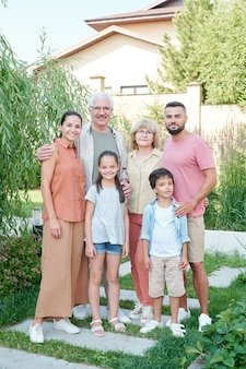晴れた夏の日に裏庭に立っている6人の多世代家族の垂直フルショットの肖像画