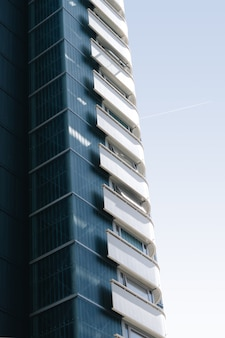 Vertical of a glass building with white balconies under the blue sky