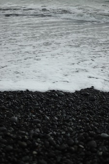 A vertical grayscale shot of beach waves coming up on the shore