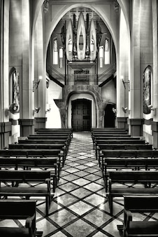 Vertical grayscale shot of the interior of an old historical christian church