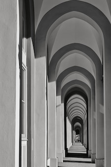 Vertical grayscale shot of a long corridor with multiple arch-shaped columns